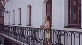 américa latina : Portrait of a cute and gorgeous latin women in a fashion dress standing on the balcony of the restaurant and drinking a cocktail Stock Footage