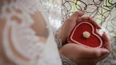 Beautiful womans hands holding heart shaped engagement ring box. Bride holding a heart shaped gift box in her hands Стоковые видеозаписи