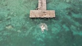 salto : BACALAR, MEXICO, 06 OCTOBER 2017: Young man jumping from wooden pier into lake - shot from drone