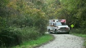 navigation : Ambulance on rescue mission in a remote narrow trail in the wood. The yellow sign says trail narrows visible in full size