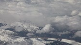 weather : Aerial view from an airplane over the west coast of the US, mountains covered with snow, and frozen lakes, lots of clouds, realtime. Stock Footage