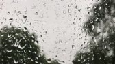 deštivý : Close up view of water drops falling on glass. Rain running down on window.