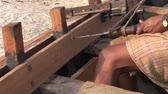 drilled : indian worker with primitive old drill drilling new boat wood
