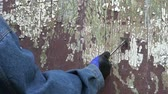 scrapper : worker hand scrapping old cracked paint from wooden door Stock Footage