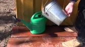 trabalho : gardener in farm pour water in plastic watering can near well