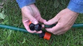 vazamento : gardener hands connecting watering hose on the lawn