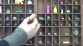 wood : Hand  placing ceramic beads and paint bottles in shelf
