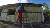 worker with helmet insulating with rock wool wooden house wall