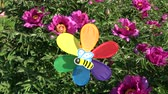 Rainbow colors decorative windmill toy near blossoming peony bush in spring garden and wind Стоковые видеозаписи