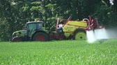 Farm tractor spraying with chemicals  wheat field in spring Стоковые видеозаписи