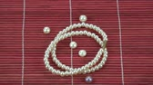 necklace : Rotating small String of pearls on red bamboo mat background Stock Footage