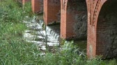 parede de tijolos : Small water flow from old historical red bricks lake dam Stock Footage