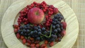crab apple : Rotating in wooden plate northern grapes, wild rose hips,apples and rowan berries on bamboo mat