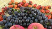 hrozný : Rotating healthy food fruits background. Northern grapes, wild rose hips and red apples