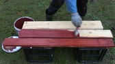 malarz : Worker paint in red new wooden planks in garden