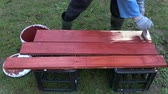 kereste : Worker paint wooden planks in red