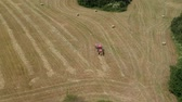 Red tractor on summer field rake dry hay, aerial view