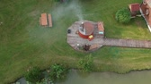 Outdoor Hot water tub and pond near wooden bathhouse, aerial view