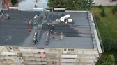 Two workers repair waterproofing apartment flat house roof, aerial view 무비클립