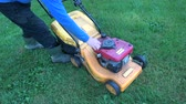jardineiro : gardener starting lawn mower  on garden grass Vídeos