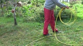 gardener in autumn yard wrap rubber yellow water hose
