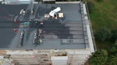 Two workers repair flat house roof in city, aerial view 무비클립