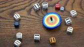 dadi : Various game dice collection on oak background and one metal whirligig top spin in motion Filmati Stock