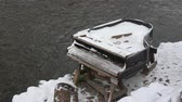 Broken derelict snowy piano musical instrument near winter river