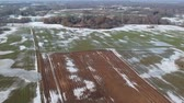 Early spring farmland fields panorama with frozen water puddles and last snow, aerial view