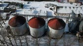 Old industrial grain silos grain storage tanks from drone in winter, aerial view