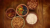 Healthy breakfast. Stop-motion. Granola. Oatmeal, barley flakes. Nuts: hazelnuts, almonds, cashews. Dried fruits: raisins, dates, dried apricots. In clay bowls on a wooden background. Top view. 4k video.