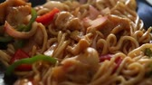 green onion : Chinese dish in a black plate noodles with onions and chicken on the table