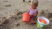 little : baby girl in purple swimsuit play in the sand with ball and wind on the beach