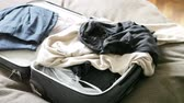 clothe : man thrown clothes and toothbrush in  suitcase and pulled out of it