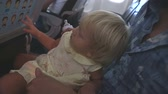 travessura : small blonde child plays pranks sitting on fathers knees in airplane Vídeos