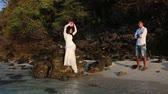 manmetro : brunette bride sits on rock in sea and lifts hands with bouquet