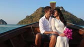 manmetro : brunette bride in white wedding dress and handsome groom float in longtail boat to island at sunrise