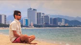 manmetro : young handsome guy in white and sunglasses operates phone sitting on sand beach by sea water against resort city