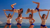 spirit : closeup squad of cute cheerleaders in white blue uniform demonstrates stunt Swedish falls and smiles against azure sea