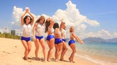spirit : cute cheerleaders in white blue uniform stand in line wave hands and run into water on beach against azure sea Stock Footage