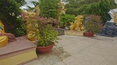 meditation : panorama of buddhist temple square with different god statues among tropical plants in Vietnam