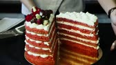 confectioner hands cut down red decorated cake into two parts Stok Video