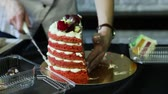 confectioner hands cut down half of red decorated cake