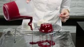 confectioner pour out red glaze on frozen desserts blanks
