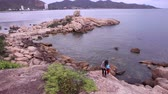 travessura : KHOANG NHA TRANG  VIETNAM - JUNE 20 2015: Vietnamese guy and long-haired brunette girl climb up rocky seashore near resort city and play pranks on June 20 in Khoang Nha Trang