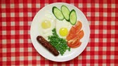 ervilha : Fried eggs with sausage, peas and fresh vegetables on red table cloth