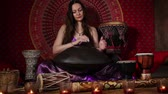meditation : Dolly video shot of woman playing hand pan indoors. Audio included