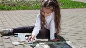 play video game : Little girl draws with chalk on the pavement in the street  at sunny day Stock Footage
