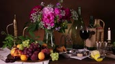 vintage : Still life with fresh flowers, burning candle and fruit vase on dark brown background in Dutch style