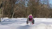 бросание : Little girl having fun playing in the snow in winter city park Стоковые видеозаписи